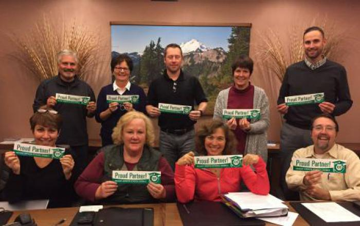 Mount Vernon Public Schools Foundation members holding Proud Partner bumper stickers